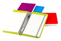 Colourful notebooks with ballpoint pen. Colourful notebooks with open notebook and ballpoint pen isolated on white background Stock Photography