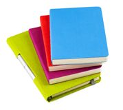 Colourful notebooks with ballpoint pen. Colourful notebooks with open notebook and ballpoint pen isolated on white background Royalty Free Stock Image