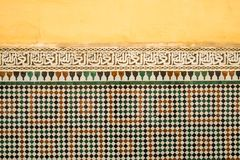 Colourful old Moroccan yellow painted wall with a band of Islamic calligraphy above zellige tilework. stock images