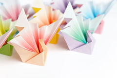 Colourful origami birds. A group of colourful origami birds facing the same direction, on a white background. High key and shallow depth of field Royalty Free Stock Photos