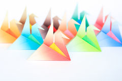 Colourful origami birds. A group of colourful origami birds facing the same direction, on a white background. Shallow depth of field stock photos
