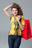Colourful outfit holding a red shopping bag, smil. Portrait of a young woman holding in one hand a red shopping bag and the other one in her hair. she is Stock Photography