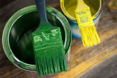 Colourful paint cans and paintbrushes on the floor viewed from above. Closeup royalty free stock photos