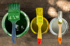 Colourful paint cans and paintbrushes on the floor viewed from above. Colourful paint cans and three paintbrushes on the floor viewed from above royalty free stock images