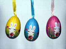 Colourful panted plastic easter eggs with white bunnies in a row Stock Photo