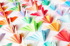 Colourful paper birds. A group of colourful origami birds facing the same direction. High key soft focus Stock Photo