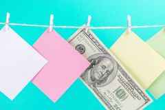 Colourful paper cards and money hanging rope isolated on blue background. Place for your text royalty free stock photography