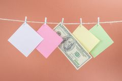 Colourful paper cards and money hanging rope isolated on brown background. Place for your text royalty free stock photo