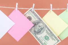 Colourful paper cards and money hanging rope isolated on brown background. Place for your text stock image