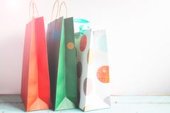 Colourful paper shopping bags on table with sunset flare, Soft f. Ocus royalty free stock photos