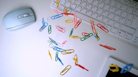 Colourful paperclips falling in the middle of a white office desk. Many colourful paperclips falling in the middle of a white office desk in slow motion stock video footage