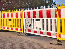 Colourful Parking Barriers With Tow Away Zone Sign. Modern parking road closure barriers, with red and white reflective safety patches and a tow away zone sign royalty free stock photo