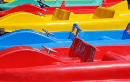 Colourful pedalos. Bright colourful red yellow and blue pedalos in a row royalty free stock image