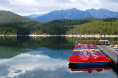 Colourful Pedalos at Lake Eibsee, Germany. On the right is a landing stage with colourful pedalos at lake Eibsee near Garmisch-Partenkirchen, Bavaria, Germany Stock Images