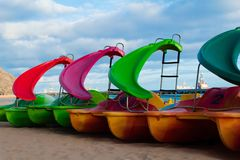 Colourful pedalos on Las Teresitas beach. In Tenerife, Canary Islands, with blu, cloudy sky. Yellow, red, pink, orange and green royalty free stock photos