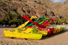 Colourful pedalos on Las Teresitas beach. In Tenerife, Canary Islands, with mountain behind. Yellow, red and green royalty free stock image