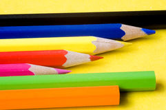 Colourful pencils. In a row isolated on yellow Royalty Free Stock Images