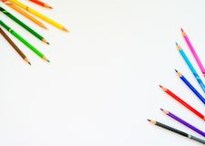 Colourful pencils on white paper background. Copy space for text.  royalty free stock photo