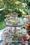 Colourful petit fours on a cake stand with bokeh. Pastel coloured petit fours on a delicate silver cake stand in a garden setting with bokeh background Stock Image