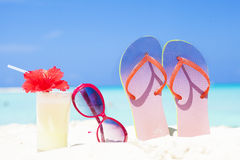 Colourful picture of flip flops, pina colada cocktail with hibiscus and pink sunglasses near the beach Stock Photography