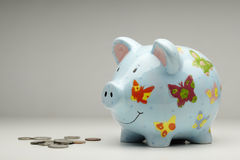 Colourful piggy bank with money. On plain background Royalty Free Stock Photography
