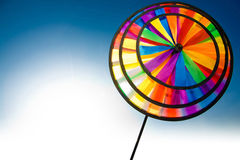 Colourful pinwheel. Plastic colourful pinwheel on the blue and white background Royalty Free Stock Images