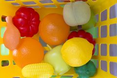 Colourful plastic toy veggies and fruit food. Close up on a yellow basket stock photos