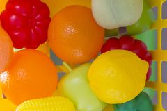 Colourful plastic toy veggies and fruit food. Close up on a yellow basket stock image