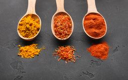 Colourful powder spices in spoons on table royalty free stock image