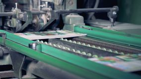 Colourful printed newspapers are getting their edges cut off by a factory mechanism. 4K stock footage