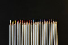 Colourful rainbow pencils for drawing on the black background. Colourful pencils for drawing and school art on the dark background. Office creativity equipment Stock Photography