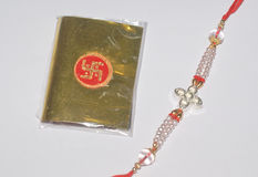 A colourful Rakhi and a golden packet. A colourful Rakhi with a golden packet having Swastik symbol containing red vermilion and sacred rice grains Stock Photo