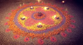 A colourful rangoli made during Diwali 2017. A vibrant and colourful Rangoli with beautifully lit lamps and adorned with flower petals, during Diwali Royalty Free Stock Photos