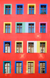 Colourful red building facade. A red building facade with colourful windows Stock Image