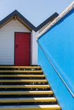 Colourful red door, with each one being numbered individually, of white beach houses on a sunny day, a view looking up the yellow Royalty Free Stock Photos