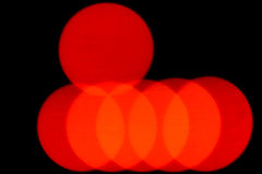 Colourful red light bokeh. Of overlapping circles on a black background with copyspace for a festive background Stock Image