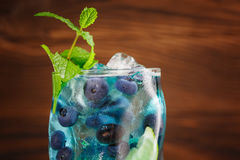 Colourful refreshing blue lagoon cocktail with mint, lime slice, ice cubes, bilberries on the wooden background. Copy space. Stock Photography