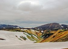 Colourful rhyolite mountains under snow, Laugavegur hiking trail, Fjallabak Nature Reserve, Highlands of Iceland, Europe. Colourful rhyolite mountains under stock photography