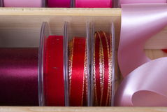 Colourful ribbons and tape. Brightly coloured fashion ribbon and tape for sewing, needlework or dressmaking on reels at a market stall . The colour mixes were Stock Photo