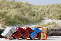 Colourful roofed wicker beach chairs at the beach. Colorful / Colourful roofed wicker beach chairs at the end of the summer season on the Island of Helgoland Stock Images