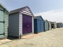 Colourful row of Beach Huts stock images