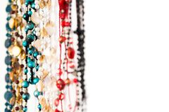 Colourful rows of beaded necklaces hanging on a white background net to negative white space. An abstract closeup of colourful beaded necklaces hanging in a row Royalty Free Stock Photography