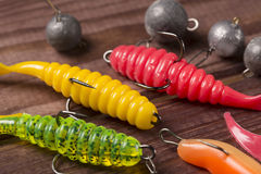 Colourful rubber fishing baits with plummets, close-up on wooden table. Selective focus Royalty Free Stock Images