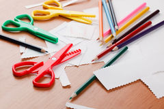 Colourful scissors and crayons. On table Stock Image