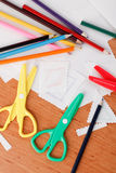 Colourful scissors and crayons. On table Royalty Free Stock Image