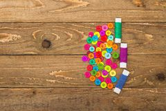 Colourful sewing buttons and rolls of thread Royalty Free Stock Photos