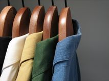 Colourful shirts in a closet. Shirts of different colors on wooden hangers in a closet stock image