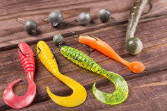 Colourful silicone fishing baits with plummets, close-up on wooden table. Selective focus Royalty Free Stock Photo