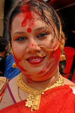 Colourful Smile. A Woman devotee smiles after applying vermilion or to another's chin during the Durga Puja festival Stock Photo
