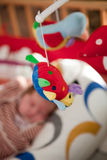 Colourful soft mobile toy on a baby crib Royalty Free Stock Photography